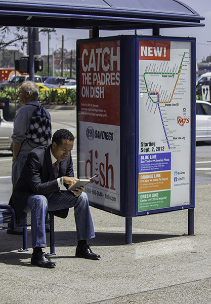man reading at bus stop with an orange in his hand - healthy, smart, and eco conscious!