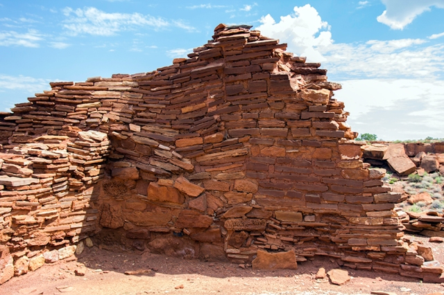 Who built this wall at Wupatki Pueblo?