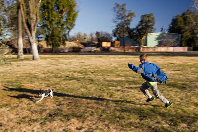 Johnathan chasing Sparky at the park