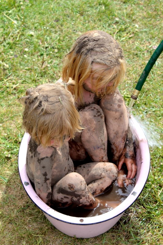 two muddy goblins sitting in a tub