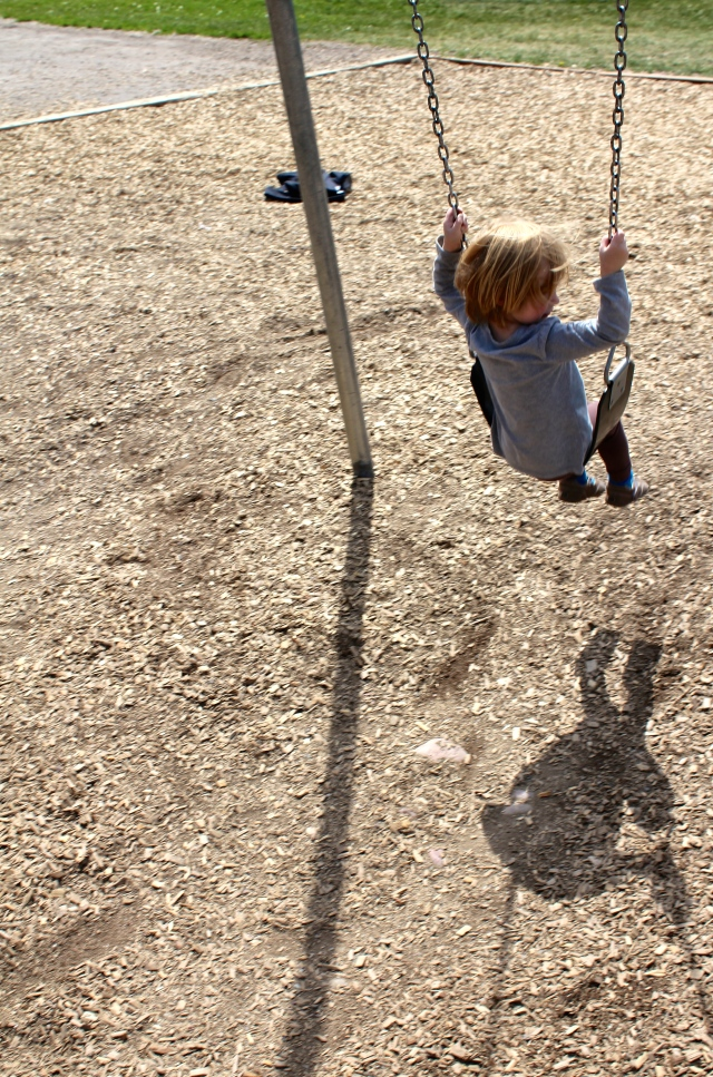 Lyra watching her shadow on the swing