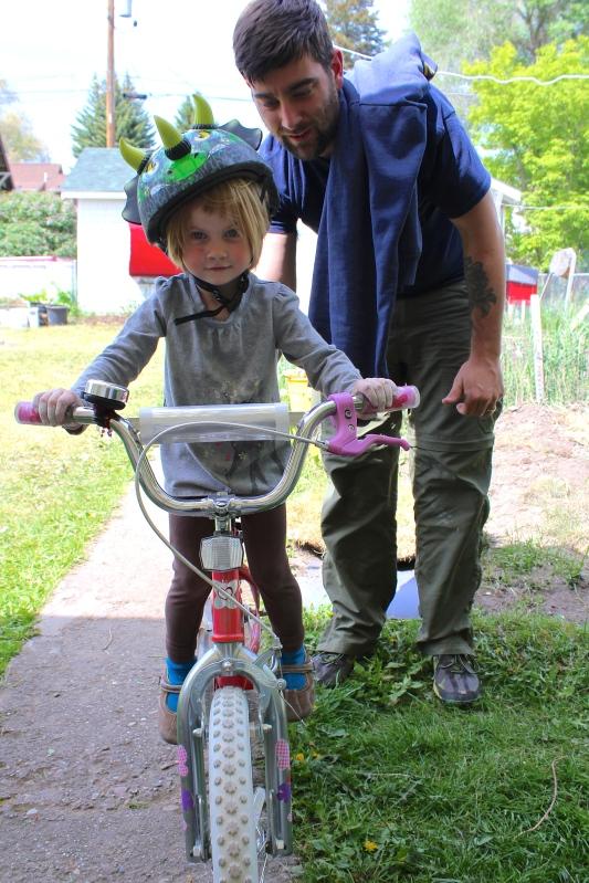 Caleb holding up Lyra on Sammi's bike