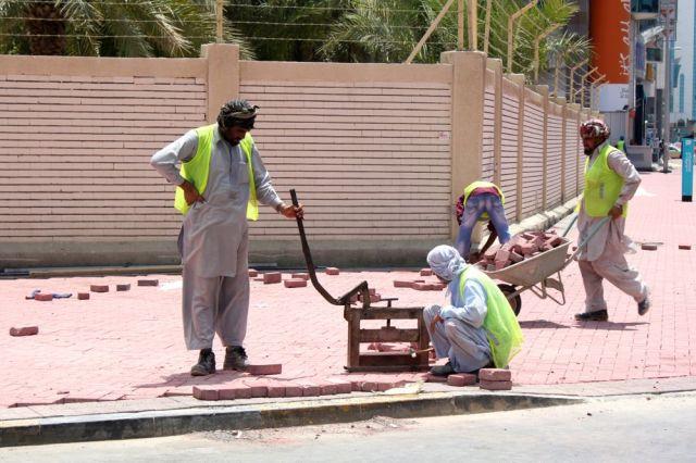 masons re-bricking the sidewalk