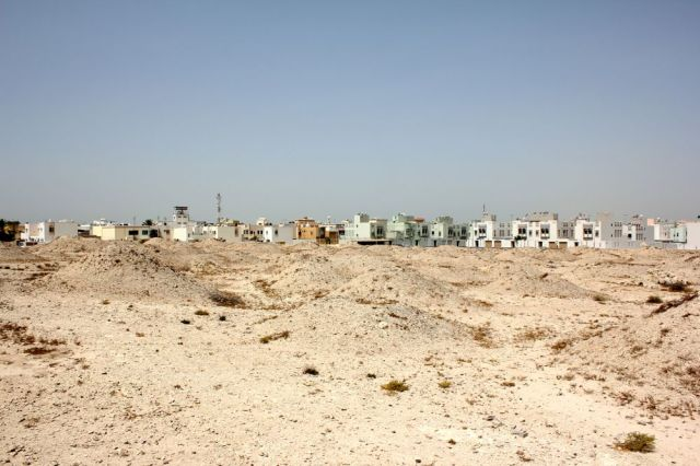 ancient burial mounds in front of modern houses