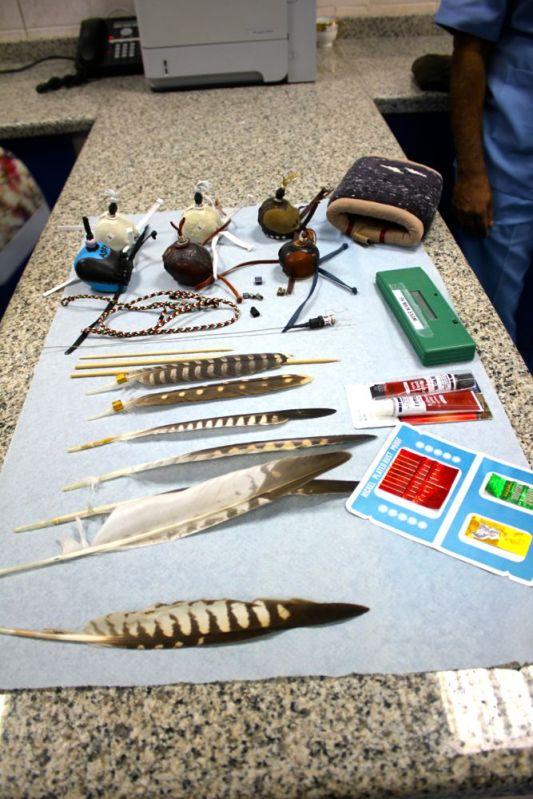 feathers, caps, needles, chopsticks, super glue, GPS transmitter, and arm sleeve